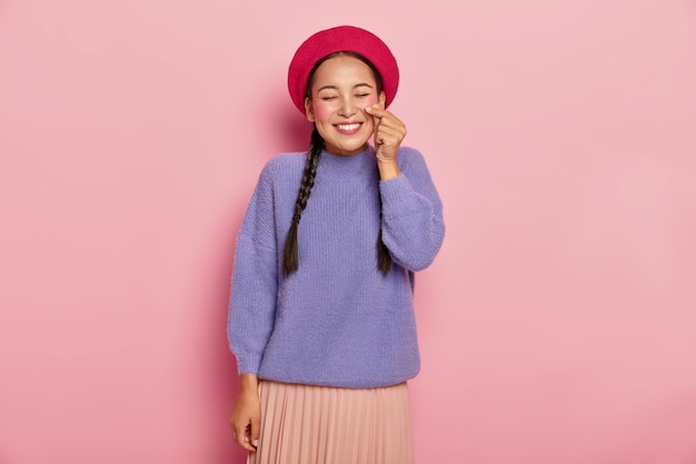 Tevreden gelukkige aziatische vrouw vormt klein hart met handen, maakt koreaans als teken, draagt rode baret, casual trui en rok, lacht aangenaam, in goed humeur, geïsoleerd over roze muur
