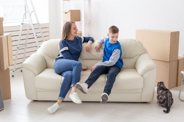 Tevreden gelukkige blanke alleenstaande moeder en zoon communiceren graag over het ontwerp van het nieuwe huis