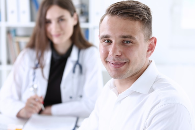 Tevreden gelukkige knappe glimlachende mannelijke patiënt met arts
