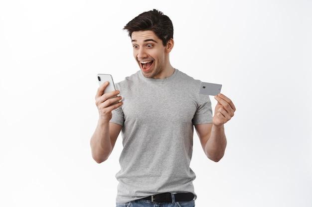 Tevreden gelukkige man die naar het smartphonescherm kijkt, creditcard toont, opgewonden glimlacht, online bestelling plaatst, winkelen in app, witte muur