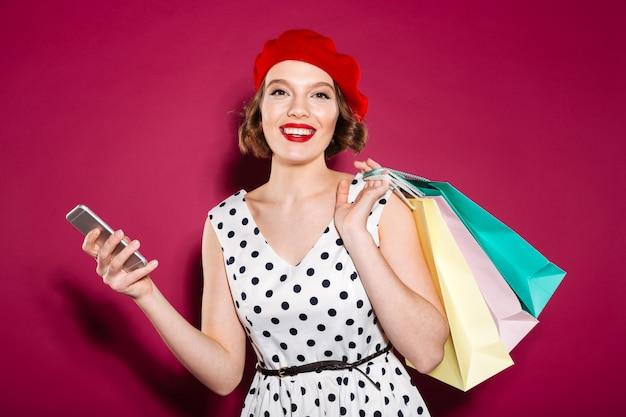 Tevreden gembervrouw in de pakketten en smartphone van de kledingsholding terwijl het bekijken de camera over roze