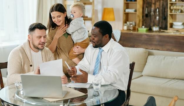 Tevreden gezin met kleine jongen met bezoek van afro-amerikaanse adviseur die thuis overleg over hypotheek geeft