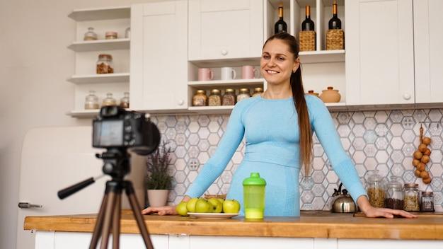 Tevreden gezond jong meisje dat haar videoblog-aflevering over gezond eten opneemt terwijl ze thuis in de keuken staat. vrouw is vriendelijk en lacht
