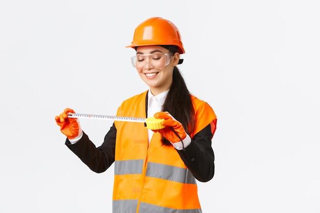 Tevreden glimlachende aziatische vrouwelijke architect behaalt goede resultaten, kijkt tevreden naar meetlint na het meten van de lay-out in het bouwgebied, staat in een veiligheidshelm en reflecterende kleding