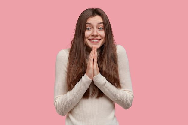 Tevreden glimlachende dame heeft een smekende uitdrukking, houdt de handpalmen tegen elkaar gedrukt, bidt voor al het goede, heeft lang donker haar, draagt vrijetijdskleding
