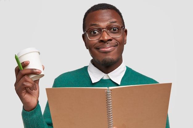 Tevreden glimlachende hipster-student draagt een ongemakkelijke bril, schrijft notities van ontwerpproject, draagt afhaalkoffie, spiraalvormig notitieboekje en pen
