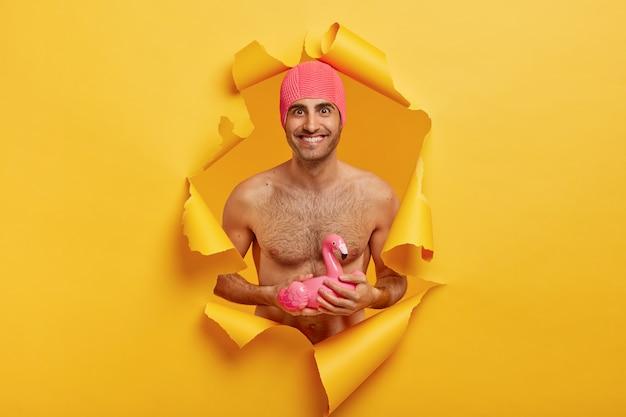 Tevreden glimlachende man met blote torso, draagt roze rubberen badmuts, klaar voor de zomervakantie