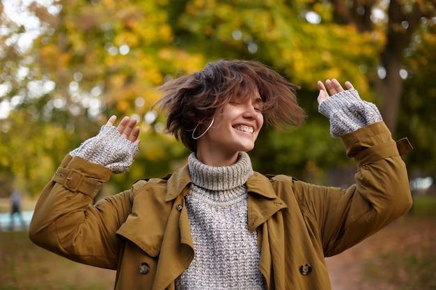 Tevreden goed uitziende jonge bruinharige vrouw die met haar korte haar zwaait en de handen omhoog houdt, breed glimlachend met gesloten ogen terwijl ze over wazig park staat