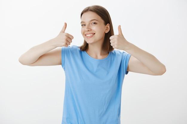 Tevreden, goed uitziende vrouw die goedkeurend glimlacht en duimen toont, garandeert kwaliteit