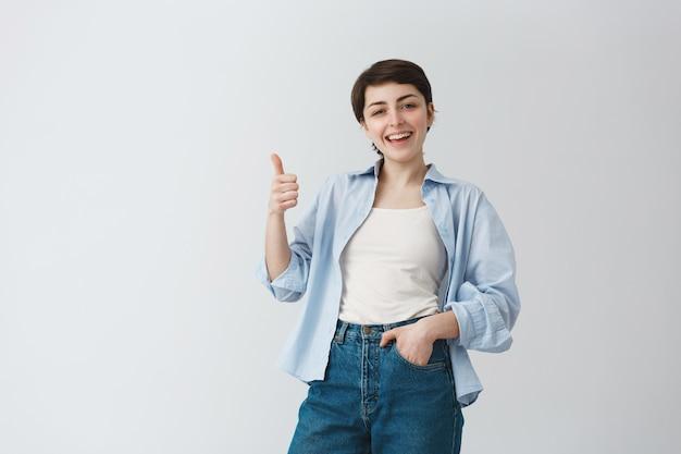 Tevreden goed uitziende vrouw met kort haar met thumbs-up in goedkeuring, lof goede keuze