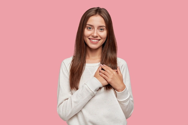 Tevreden gulle brunette vrouw met tedere glimlach, houdt beide handpalmen op de borst