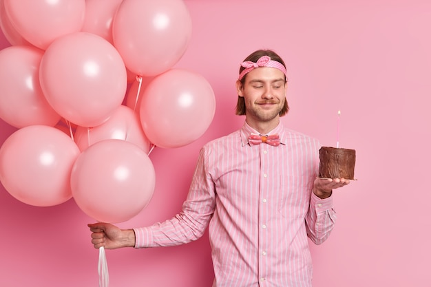 Tevreden hipster man gaat iemand feliciteren houdt chocoladetaart met brandende kaars bos van opgeblazen ballonnen draagt feestelijke kleding geniet van vakantie vieren geïsoleerd over roze muur