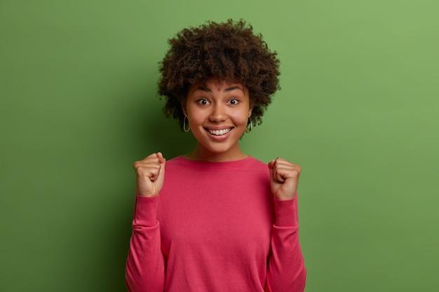 Tevreden, hoppige vrouw met krullend haar wacht op belangrijke resultaten, balt vuisten tijdens de viering, geniet van positief nieuws, glimlacht gelukkig, blij om doel te bereiken, draagt roze trui, geïsoleerd op groene muur