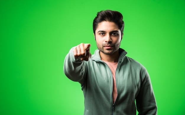 Tevreden indiase man presenteren, wijzen, weergeven of adverteren met lege handen of vingers. geïsoleerd staan