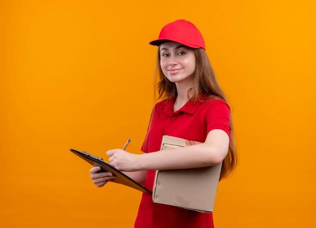 Tevreden jong bezorgmeisje in rode uniforme holdingsdoos en schrijven op klembord op geïsoleerde oranje ruimte