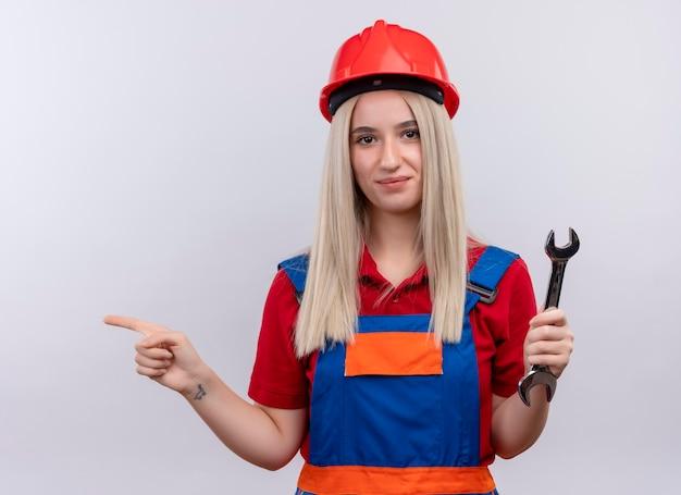 Tevreden jong blond ingenieursbouwersmeisje in uniform met steeksleutel die naar linkerkant op geïsoleerde witte ruimte richt