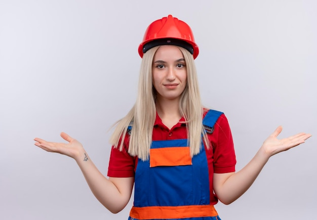 Tevreden jong blond meisje van de ingenieursbouwer in eenvormig die lege hand op geïsoleerde witte ruimte tonen Gratis Foto