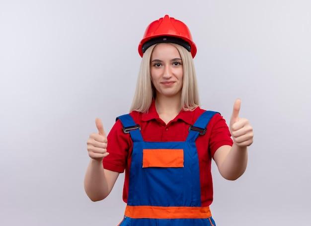 Tevreden jong blond meisje van de ingenieursbouwer in uniform duimen opdagen op geïsoleerde witte ruimte met exemplaarruimte Gratis Foto