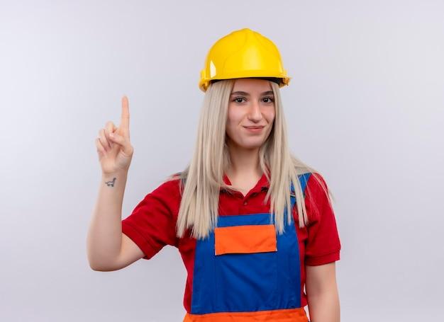 Tevreden jong blond meisje van de ingenieursbouwer in uniform met opgeheven vinger op geïsoleerde witte ruimte Gratis Foto