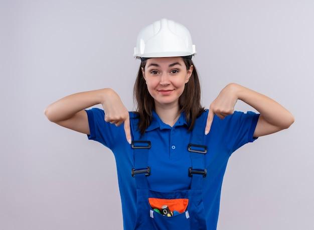 Tevreden jong bouwersmeisje met witte veiligheidshelm en blauw eenvormig punt naar beneden met beide handen op geïsoleerde witte achtergrond
