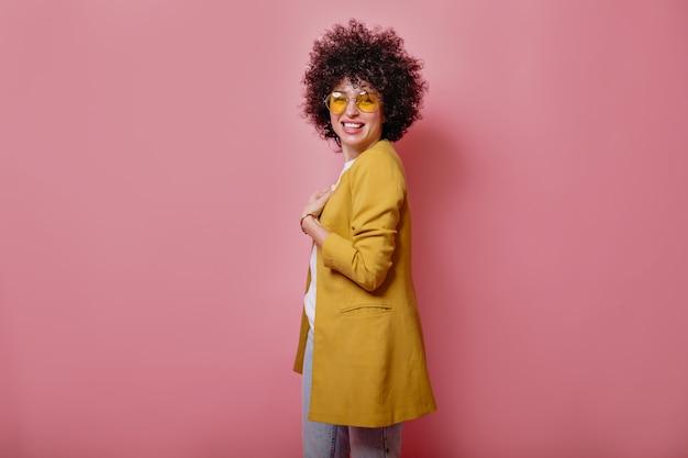 Tevreden jong glimlachend meisje die met krullen geel jasje dragen die voorzijde over roze muur bekijken