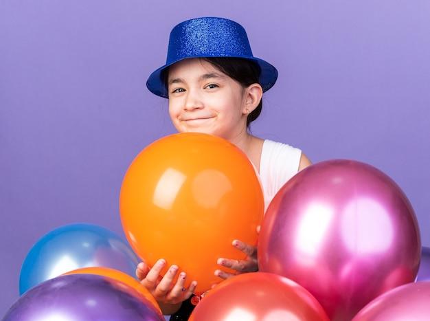Tevreden jong kaukasisch meisje met blauwe feestmuts die zich met heliumballons bevindt die op purpere muur met exemplaarruimte worden geïsoleerd