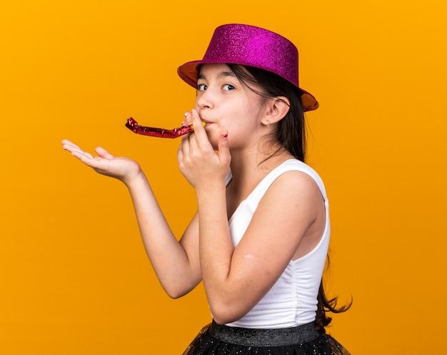 Tevreden jong kaukasisch meisje met purpere partijhoed blaast partijfluit en houdt hand open geïsoleerd op oranje muur met exemplaarruimte