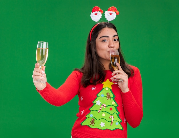 Tevreden jong kaukasisch meisje met santa hoofdband houdt en drinkt glazen champagne geïsoleerd op groene achtergrond met kopie ruimte
