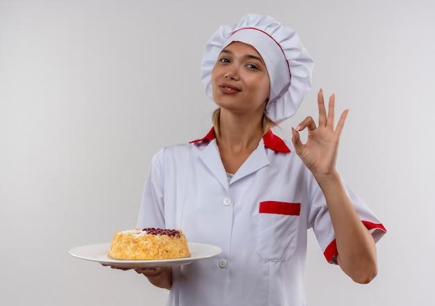 Tevreden jong kokwijfje die cake van de chef-kok de eenvormige holding op plaat dragen die okgebaar op geïsoleerde witte muur met exemplaarruimte tonen