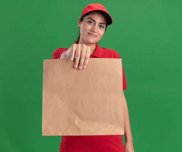 Tevreden jong leveringsmeisje die eenvormig en glb dragen die document voedselpakket vasthoudt aan voorzijde geïsoleerd op groene muur