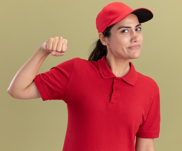 Tevreden jong leveringsmeisje die eenvormig met glb dragen die sterk gebaar tonen dat op olijfgroene muur wordt geïsoleerd