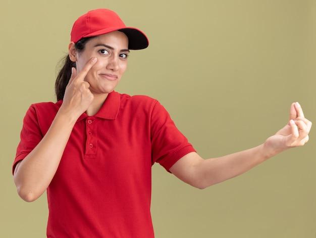 Tevreden jong leveringsmeisje die eenvormig met glb dragen die vinger op oog zetten die uiteindegebaar tonen dat op olijfgroene muur wordt geïsoleerd