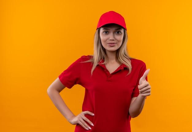 Tevreden jong leveringsmeisje die rood uniform en glb dragen die hand op heup haar duim zetten die omhoog op oranje achtergrond wordt geïsoleerd
