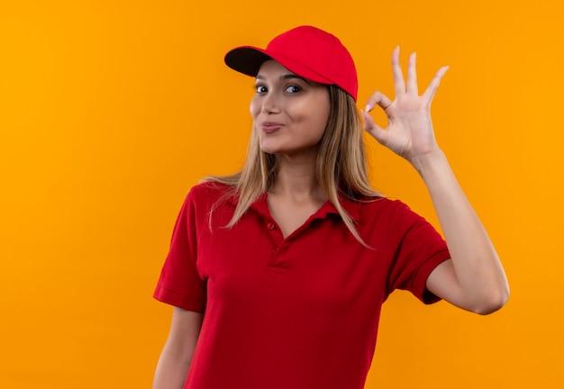 Tevreden jong leveringsmeisje die rood uniform en glb dragen die okgebaar tonen dat op oranje achtergrond wordt geïsoleerd