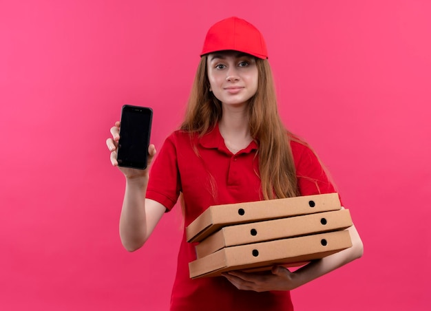 Tevreden jong leveringsmeisje in rode uniforme holdingspakketten en mobiele telefoon op geïsoleerde roze ruimte tonen