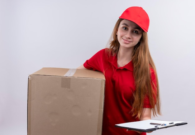 Tevreden jong leveringsmeisje in rood eenvormig holdingsdoos en klembord op geïsoleerde witte ruimte