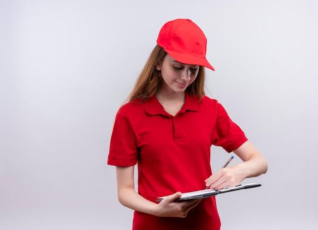 Tevreden jong leveringsmeisje in rood uniform die op klembord op geïsoleerde witte ruimte met exemplaarruimte schrijven