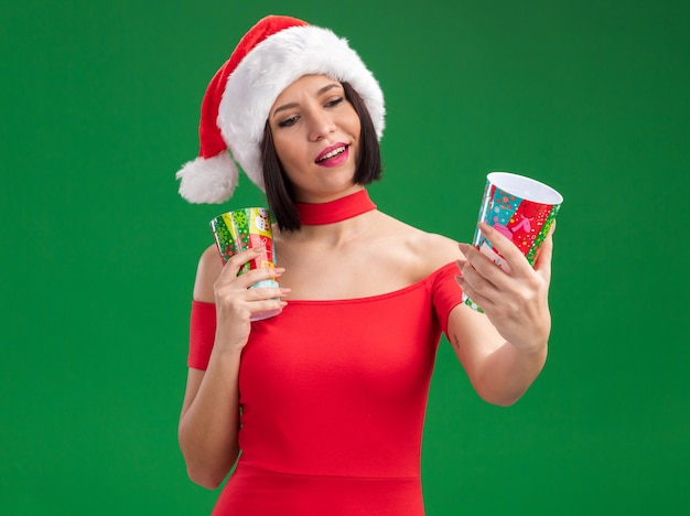 Tevreden jong meisje dat santahoed draagt die de plastic koppen van kerstmis houdt die zich uitstrekt kijken naar het geïsoleerd op groene achtergrond
