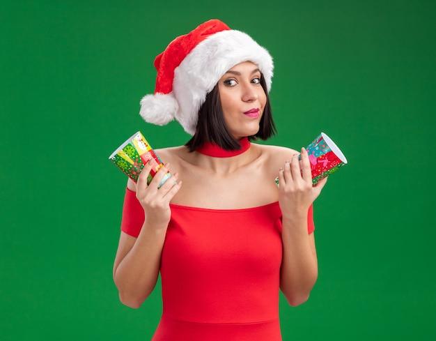 Tevreden jong meisje dat santahoed draagt die plastic kerstmiskoppen houdt die op groene muur worden geïsoleerd