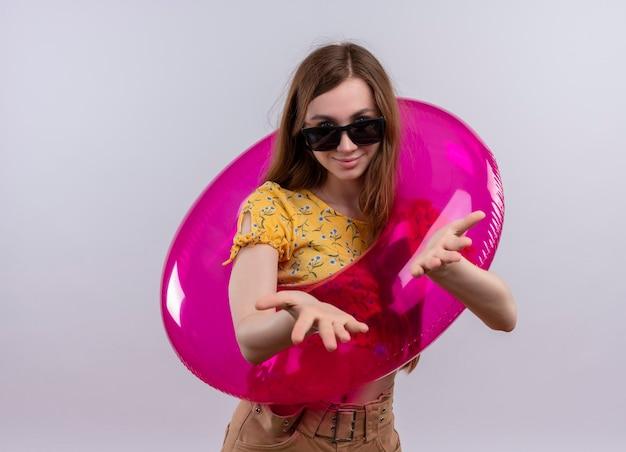 Tevreden jong meisje dat zonnebril draagt en zwemt ring die lege handen op geïsoleerde witte ruimte met exemplaarruimte toont