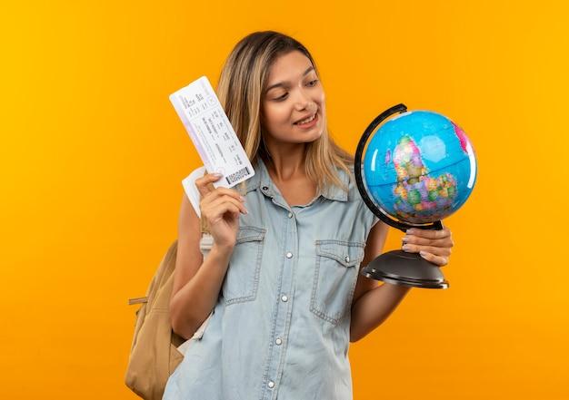 Tevreden jong mooi studentenmeisje die de bol van de achterzakholding en vliegtuigticket dragen die bol bekijken die op oranje muur wordt geïsoleerd