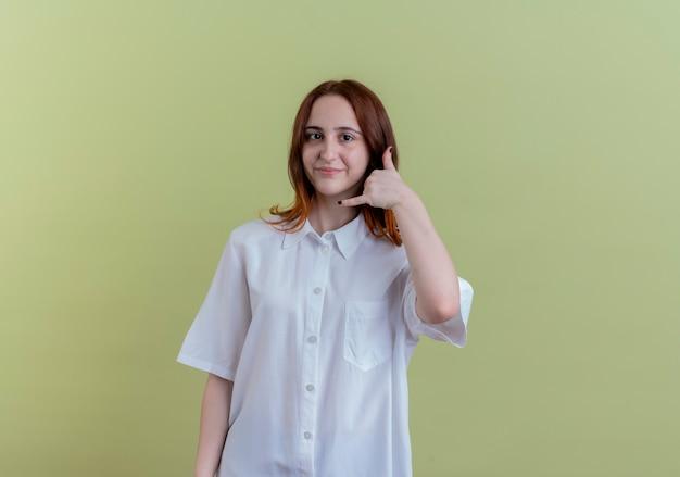 Tevreden jong roodharigemeisje die telefoongesprekgebaar tonen dat op olijfgroen met exemplaarruimte wordt geïsoleerd