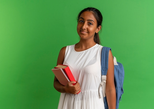 Tevreden jong schoolmeisje die rugtas draagt die boek en notitieboekje houdt