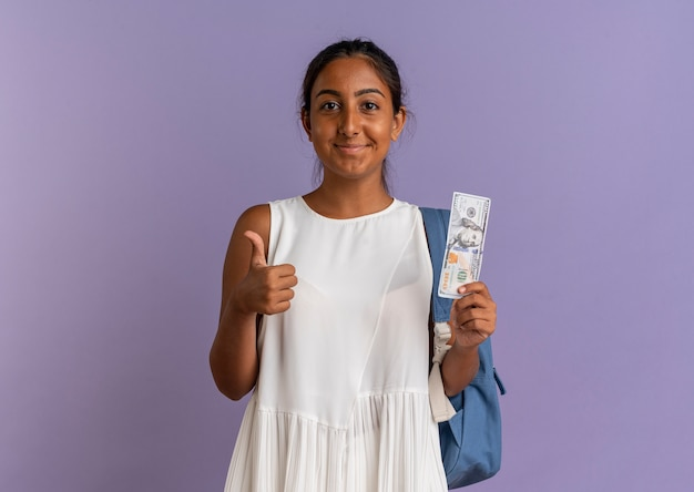 Tevreden jong schoolmeisje die rugtas draagt die geld haar duim op paars houdt