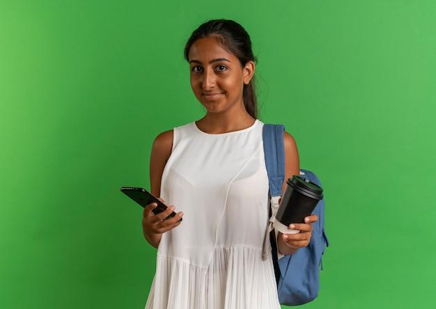 Tevreden jong schoolmeisje die rugtas draagt die kop van koffie en telefoon op groene achtergrond houdt
