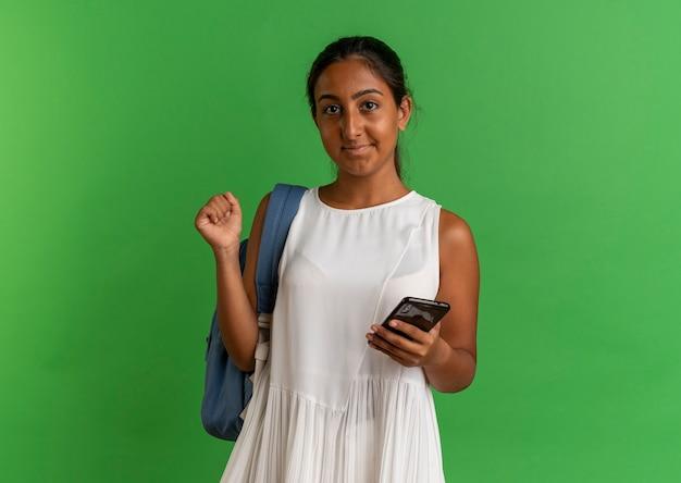 Tevreden jong schoolmeisje met telefoon en ja gebaar op groen tonen