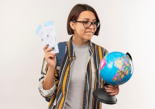 Tevreden jong studentenmeisje die glazen en achterzak dragen die vliegtuigtickets en bol bekijken die bol bekijken die op witte muur wordt geïsoleerd