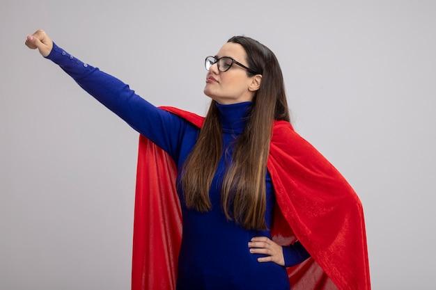 Tevreden jong superheromeisje die kant bekijken die glazen dragen die hand opheffen die op witte achtergrond wordt geïsoleerd