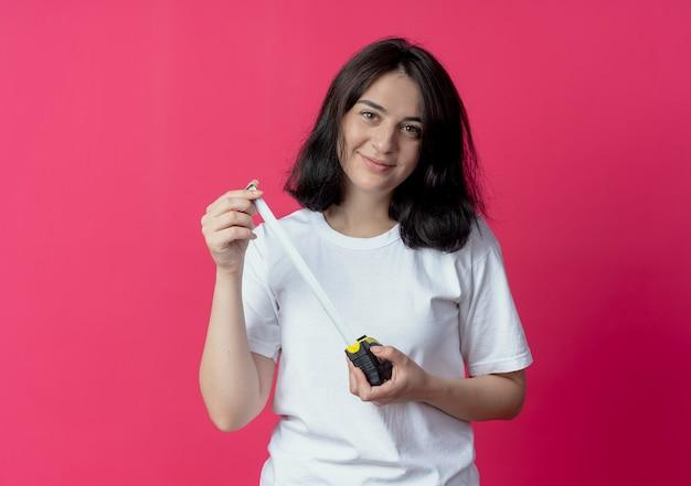 Tevreden jong vrij kaukasisch de bandmeter van de meisjesholding die op karmozijnrode achtergrond met exemplaarruimte wordt geïsoleerd