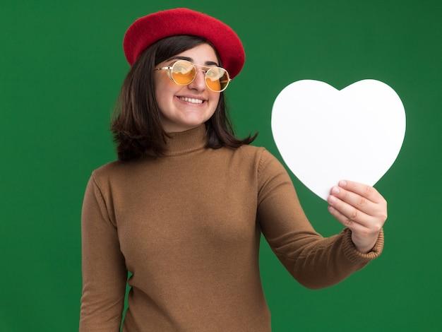 Tevreden jong vrij kaukasisch meisje dat met barethoed in zonglazen hartvorm op groen houdt